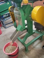 The processed beans come flying out of the machine into a bucket